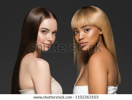 Mixed races women beauty portrait caucasian and african american two girls different skintone
