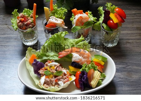 Mixed salad canapés with dressing in a plate on wooden background. Photo stock ©