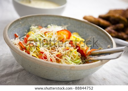 Mixed salad in a blue bowl on a table. Focus is shallow.