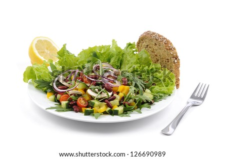 Mixed salad on a white plate and a fork, isolated against a white background