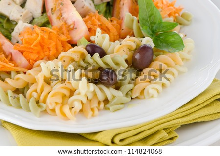 Mixed salad on a white plate and a white wood background.