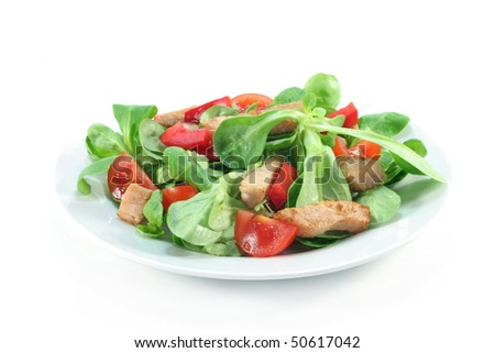 Mixed salad with chicken strips on a white background