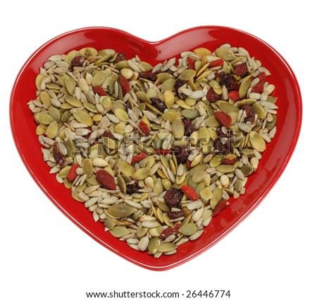 mixed seeds cereal for healthy breakfast or snacking in heart shape plate, over white