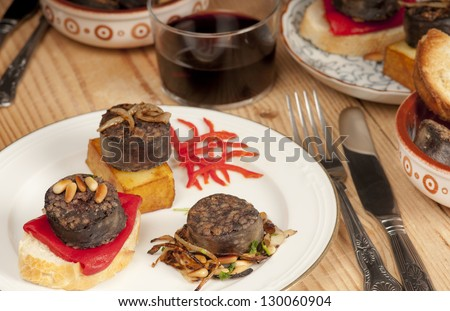 Mixed Spanish tapas with morcilla, pine nuts, confit potato, bread, toast, piquillo pepper, red, wine, rioja.