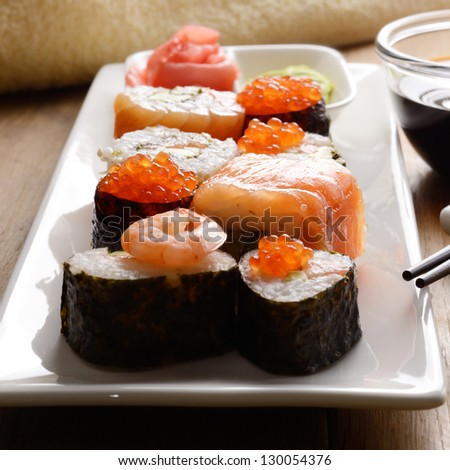 Mixed sushi on a white plate with soy sauce