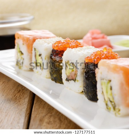 Mixed sushi on a white plate with soy sauce wasabi and ginger