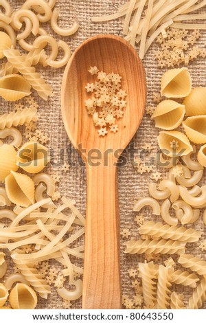 Mixed uncooked macaroni on the coarse linen fabric