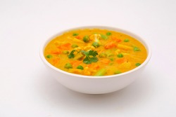 Mixed veg curry or kurma  tasty indian dish made of different vegetables like cauliflower, carrot, potato, green peas and garnished with onion pieces and mint leaf placed in a white ceramic bowl .