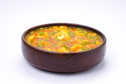 Mixed veg curry or kurma  tasty indian dish made of vegetables like cauliflower, carrot, potato, green peas and garnished with onion pieces and mint leaf in a white wooden bowl with white colour