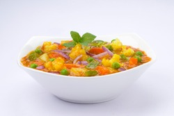 Mixed veg curry or kurma  tasty indian dish made of vegetables like cauliflower, carrot, potato, green peas and garnished with onion pieces and mint leaf placed in a white ceramic bowl with background