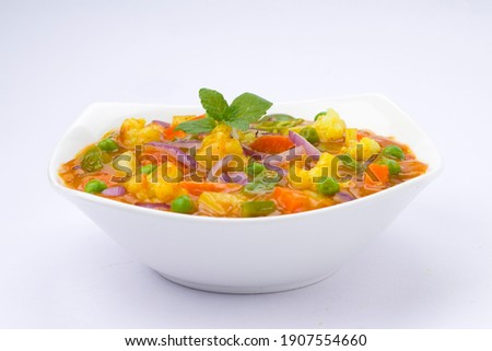 Mixed veg curry or kurma  tasty indian dish made of vegetables like cauliflower, carrot, potato, green peas and garnished with onion pieces and mint leaf placed in a white ceramic bowl with background Stock fotó ©