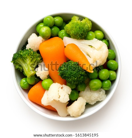 Mixed vegetables in white ceramic bowl isolated on white. Top view.