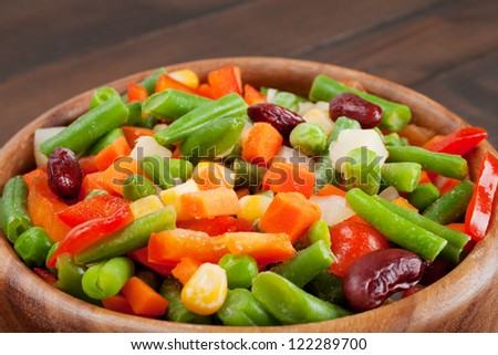 mixed vegetables in wooden bowl on kitchen table - stock photo