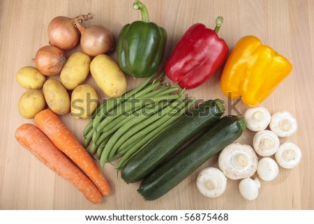 Mixed vegetables over chopping board - stock photo