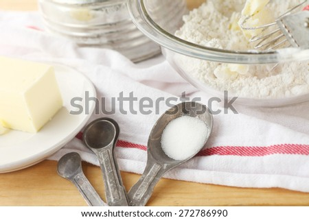 Mixing bowl with flour and butter, vintage sifter, measuring spoons and dish cloth