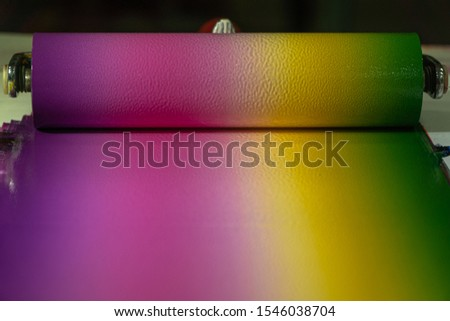 Mixing colors using a roller to rotate colors so that each color is blended together and then rolled onto the template to create graphic arts. #1546038704