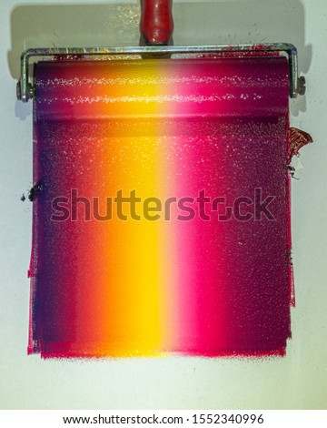 Mixing colors using a roller to rotate colors so that each color is blended together and then rolled onto the template to create graphic arts. #1552340996