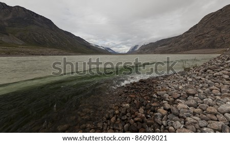 Mixing rain water and melting water rivers flowing through arctic tundra, Greenland