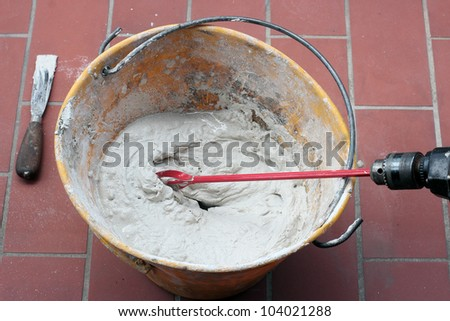 mixing Tile adhesive or cement with a power drill - stock photo