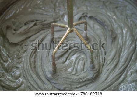 Mixing tile adhesive or cement with a power drill for garden repair works. Liquid, equipment.The solution is mixed using a construction mixer. Foto stock ©