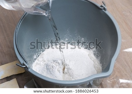 Mixing white plaster in a bucket with a stirrer. Close-up. Foto stock ©