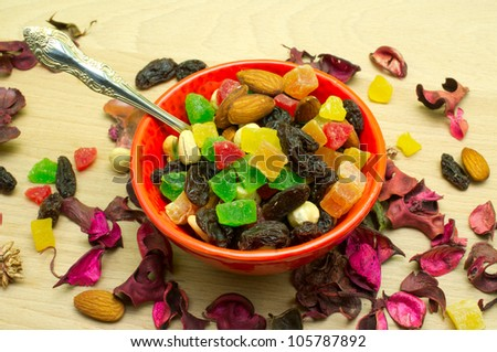 Mixture of dried fruits and nuts in a red cup with a spoon