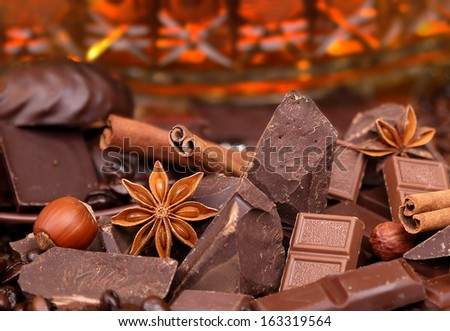 Mixture of pieces of chocolate spices and nuts close-up, selective focus