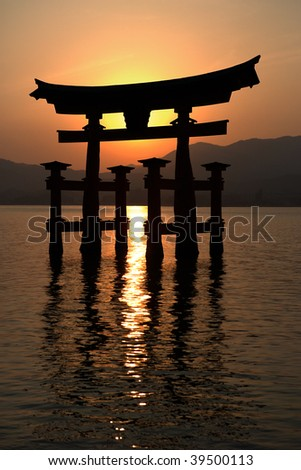 Miyajima gate silhouette at sunset. In the background the mountain range of Hirodenmiyahimaguchi/Hiroshima Prefecture.
