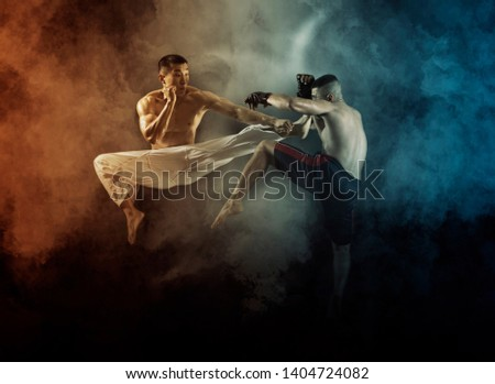 MMA boxers fighters fight in fights without rules.  Smoke background
