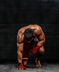 MMA Fighter Kneeling on the Floor Before the Fight