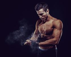 MMA Fighter Preparing Bandages For Training. Dark background