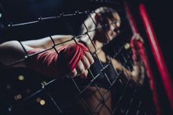 MMA is young girl in octagon during fights without rules gaining strength at grid of Boxing ring, hard clutching links fist wrapped red protective bandage. Selective focus