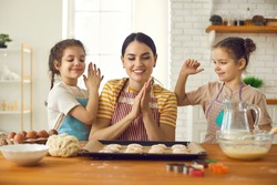 Mmm looks yummy. Happy young woman and cute little children making delicious sweet cookies at home. Smiling mother and twin daughters cooking tasty treats in the kitchen together