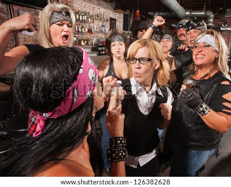 Mob of motorcycle gang members cheering on a fight with a nerd