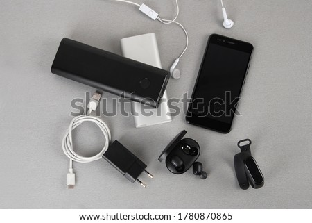 Mobile accessories include white and black power bank, wireless headphone adapter and smartwatch and type C cable Foto d'archivio ©