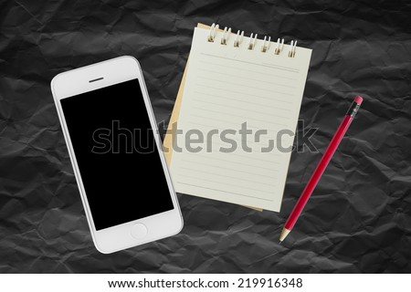 Mobile and Notebook on black paper