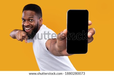 Mobile App Advertisement. Excited Black Man Showing Smartphone Empty Screen Recommending App Posing Over Yellow Studio Background, Smiling To Camera. Check This Out, Cellphone Display Mockup