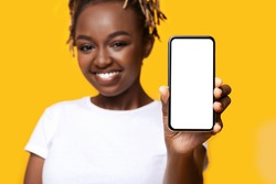 Mobile app concept. Cheerful black woman showing smartphone with blank screen over yellow background. Closeup of african american young lady smiling and holding mobile phone with white screen