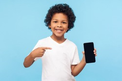 Mobile app for children. Happy excited cheerful little boy with curly hair in T-shirt pointing at cell phone and smiling at camera, showing telephone. indoor studio shot isolated on blue background