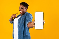 Mobile Application Ad. Excited African Woman Showing Phone Empty Screen Recommending App Standing Over Yellow Studio Background, Smiling To Camera. Cellphone Display Mockup, Check This Apps