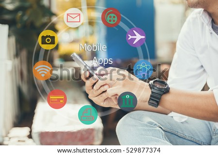 mobile apps concept.Business man hands holding touch screen smartphone outside in the park,color filter,all element graphic are made up by me #529877374