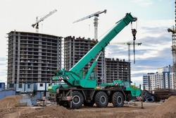 Mobile auto crane at construction site. Work of truck crane on project works. Tower cranes and builders in action. Crane for building multi-story a home