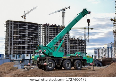 Mobile auto crane at construction site. Work of truck crane on project works. Tower cranes and builders in action