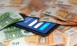 Mobile banking and finance concept: smartphone with stock exchange market application, euro banknotes. Business background. Blurred concept