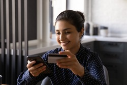 Mobile banking. Smiling mixed race female use smartphone bank card to provide fast easy payment buy goods at web shop. Hindu businesswoman pay tax online by cell being sure of personal data protection