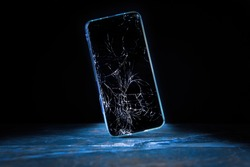 Mobile cellphone with broken glass. Smartphone falling down on the ground and broke touchscreen with beauty blue backlight and dark background