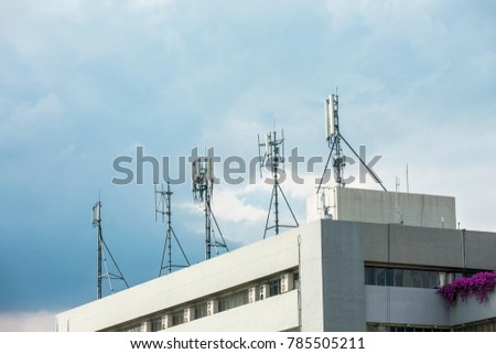 Mobile cellular telecommunication antenna network On the building block with blue sky scene.Digital audio and video transmission #785505211
