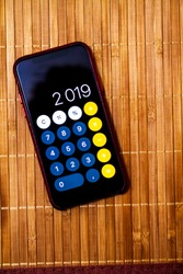 Mobile device with a calculator displaying 2019 new year on a wood table
