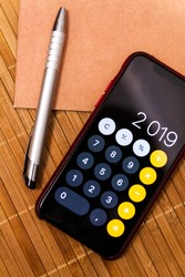 Mobile device with a calculator displaying 2019 new year on a wood table with a notebook and a pen