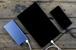 Mobile devices smartphone, tablet and power bank on wooden table. Connect of using charger. Shown use of portable charger.